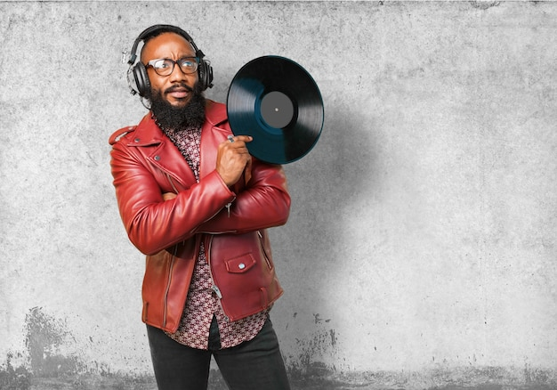 Человек в кожаной куртке, слушать музыку и проведение виниловую пластинку