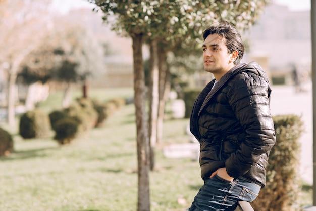 주머니에 손을 넣고 공원에 서있는 가죽 자켓 남자. 고품질 사진