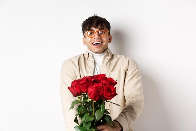 赤いバラを持って、カメラを優しく見て、幸せそうな顔で恋人を見つめ、ガールフレンドとバレンタインデーを祝って、白い背景の上に立っている愛の男