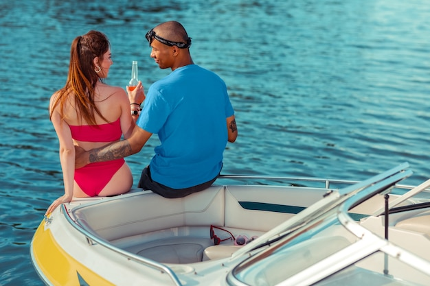 恋する男。ヨットで彼女の隣に座っている間彼の白人のガールフレンドを優しく抱きしめるロマンチックなアフリカ系アメリカ人の若い男