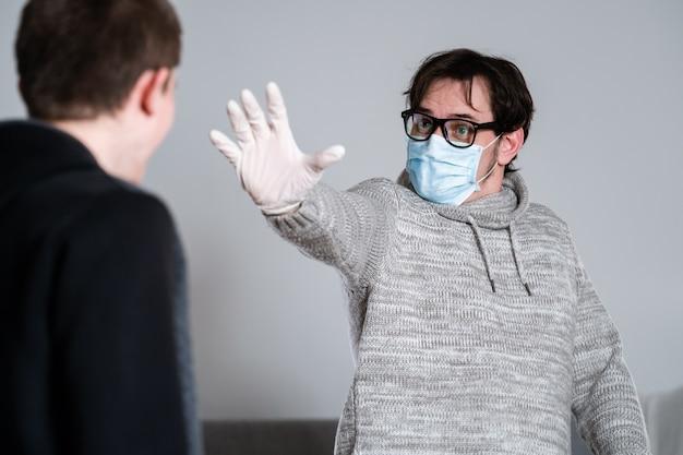 マスクと手袋をした男が手を伸ばして社会的距離を決定