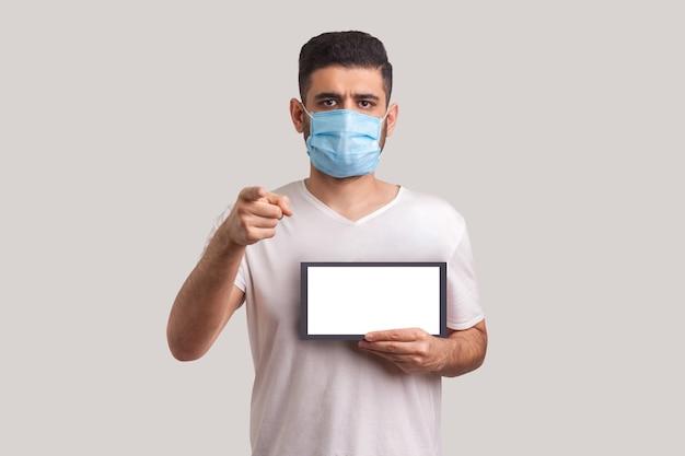 外出禁止令、カメラを指して、コロナウイルス検疫の警告を保持しているマスクの男