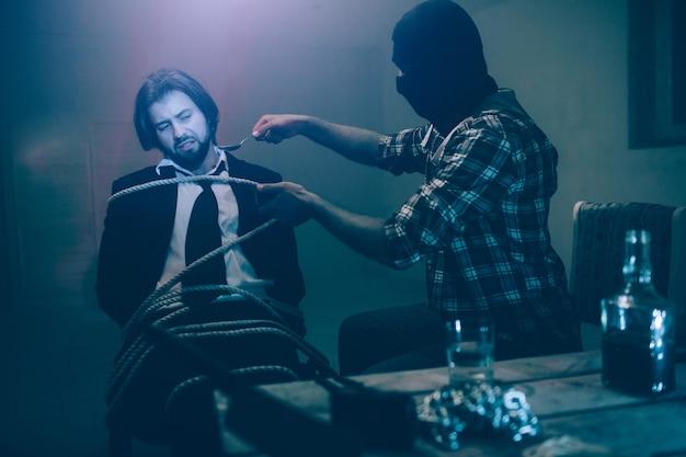 Мужчина в маске держит большую ложку у лица жертвы. бизнесмен сидит привязанным к стулу телом и смотрит на ложку. он не хочет брать это. на столе стакан с водой и цепи.