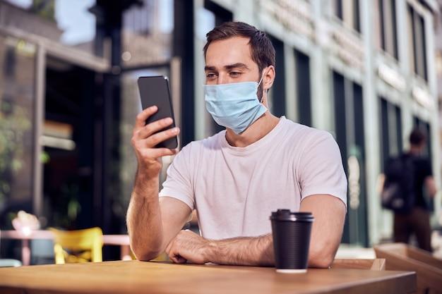マスクをした男性がスマートフォンとコーヒーを飲みながら座っている