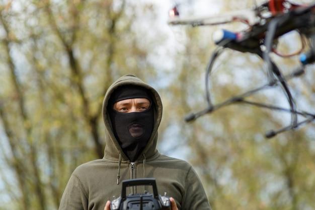 リモコンでドローンを操作するマスクの男
