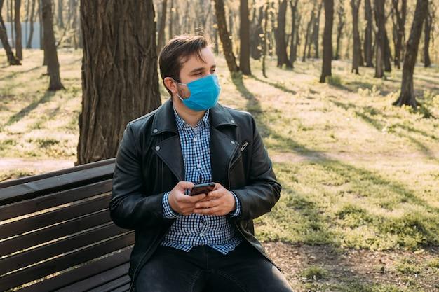 スマートフォン、ヘルスケアの概念を使用して仮面の男。コロナウイルス検疫。