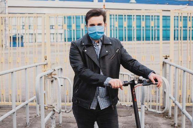 フェンスの背景に折衷的なスクーターで仮面の男