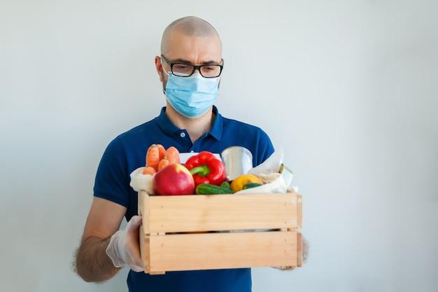 Мужчина в медицинской маске и перчатках держит коробку с едой