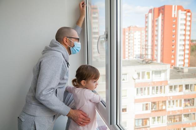 Человек в медицинской маске и его маленькая дочь, глядя на улицу