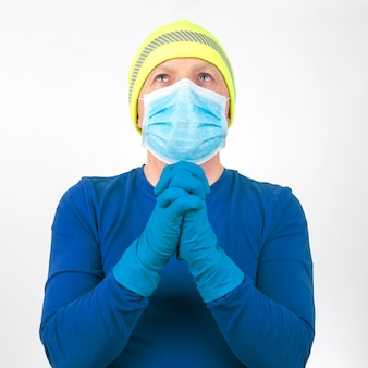 의료 마스크와 보호 장갑을 입은 남자 가기도를 위해 손을 접었습니다.