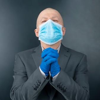 医療用マスクと保護手袋を着用した男性が祈りのために手を組んだ