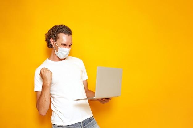 Человек в медицинской маске повседневной одежды с ноутбуком в руке радуется победе на желтом фоне