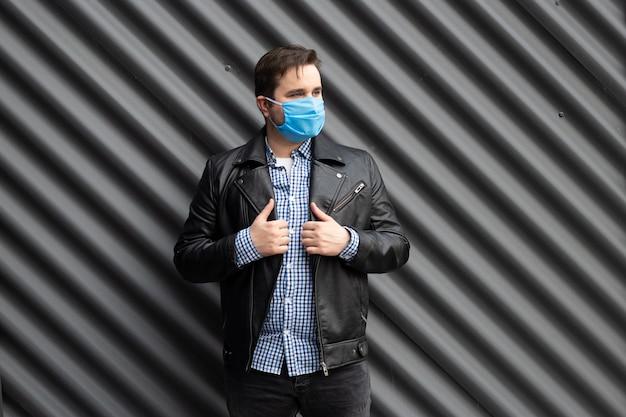 黒い壁の背景に医療マスクの男