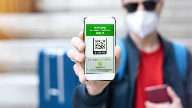 スマートフォンで国際予防接種証明書の covid-19 qr コードを表示する医療用マスクの男性