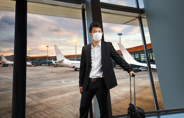 空港に立っている医療マスクの男