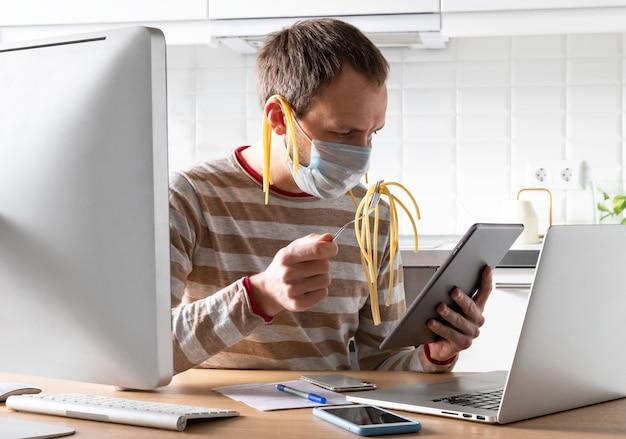 麺を耳につけた医療用マスクを着た男性。フォークを握り、ソーシャルネットワークをスクロールしながら、偽のニュースやニュースを読みます。自己隔離および隔離期間、情報流行