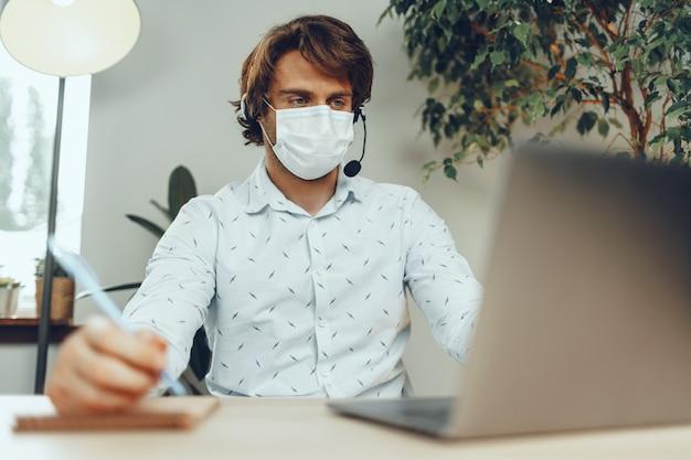 Мужчина в медицинской маске работает из дома во время карантина из-за коронавируса