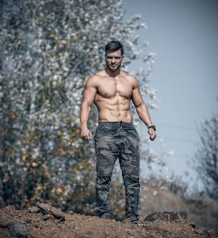 自然の背景に立っているミリタリーパンツの男。完璧な男性の体。