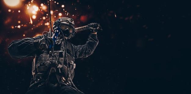 Мужчина в военной форме висит на веревке и раскачивает специальное устройство, чтобы разбивать окна