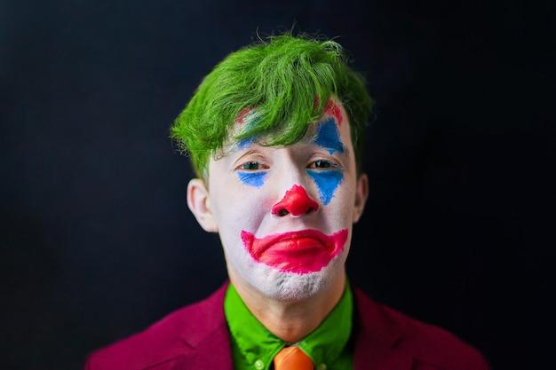 緑の髪と赤いスーツ、オレンジ色のネクタイと緑のシャツのピエロの悲しいmimeメイクコスプレの男