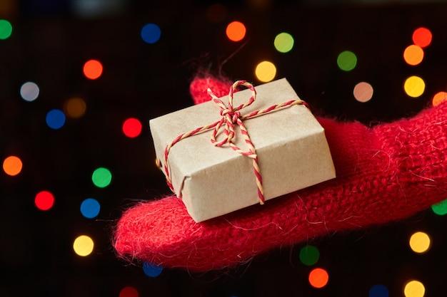 화려한 불빛에 대 한 선물 상자를 들고 벙어리 장갑에 남자