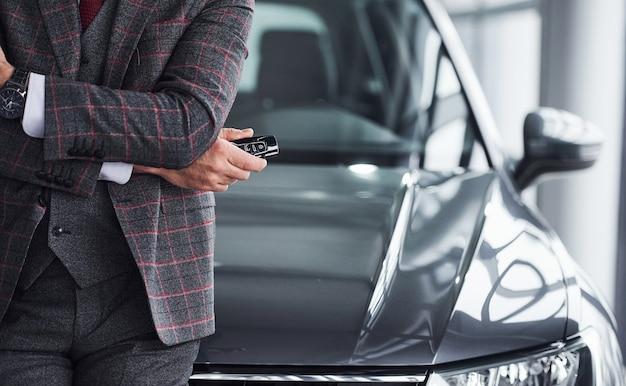 현대적인 정장을 입은 남자는 손에 열쇠를 들고 검은색 차를 마주하고 있습니다.