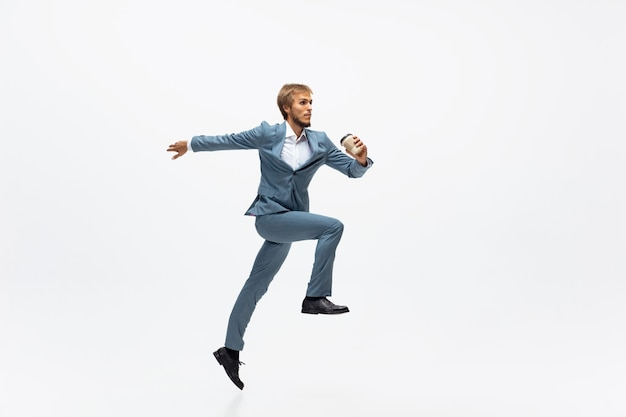 Человек в офисной одежде работает бегом на белом