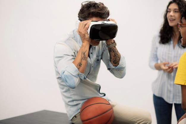 オフィスの男性は、ボールの横に座っているバーチャルリアリティメガネを使用しています