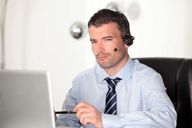 ノートパソコンとヘッドセットを持ってオフィスにいる男
