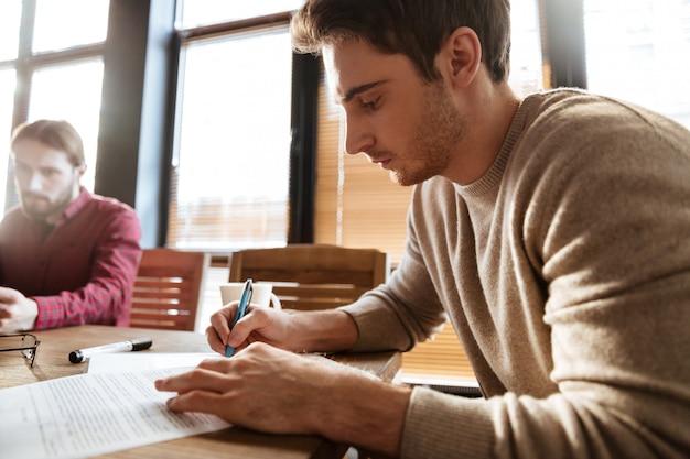 ノートにメモを書きながら働いているオフィスの人