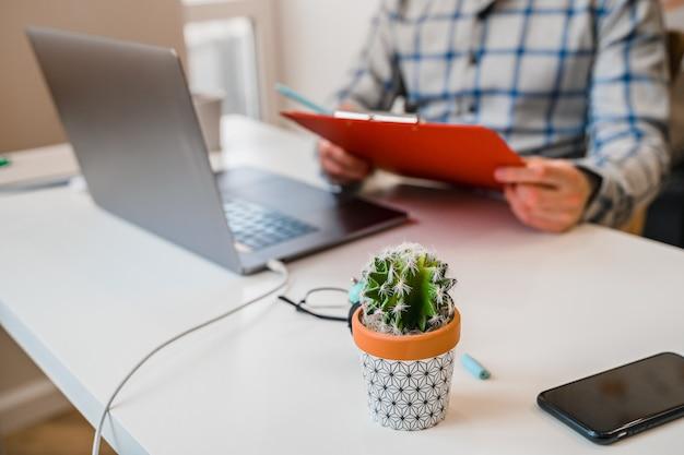 オフィスの男性はラップトップで働いており、ノートブックのプロジェクトマネージャーまたは開発者にメモをとっています
