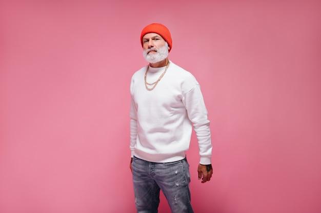 オレンジ色の帽子をかぶった男がピンクの壁にカメラをのぞき込む