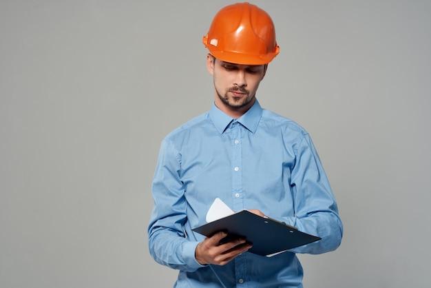 オレンジ色のヘルメットの青写真ビルダー孤立した背景の男