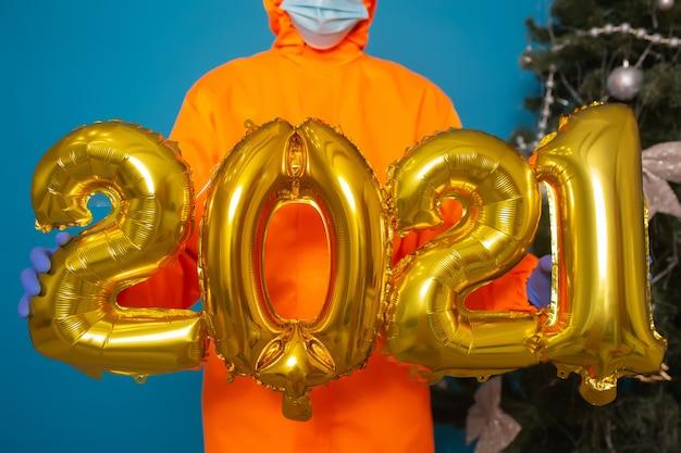 Человек в оранжевой форме с медицинской маской держит золотые гелиевые шары с цифрами 2021 год