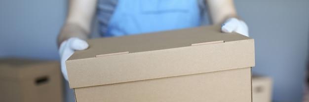 Мужчина в комбинезоне и перчатках держит большую картонную коробку в руке крупным планом. на заднем плане много картонных коробок.
