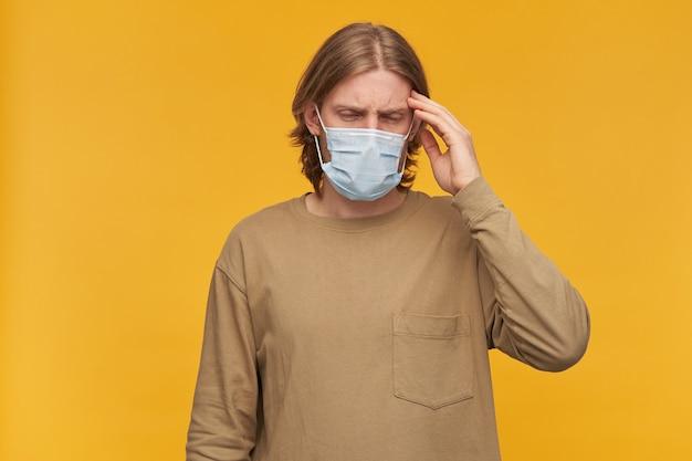 고통에 빠진 남자, 금발 머리, 수염을 가진 남자를 강조했습니다. 베이지 색 스웨터와 의료용 안면 마스크를 착용하십시오. 그의 사원을 만지고 두통으로 고통받습니다. 노란색 벽 위에 절연 스탠드
