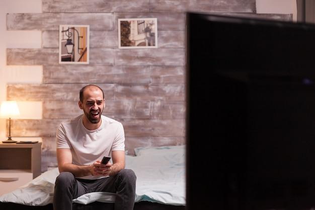 Мужчина в пижаме смеется во время просмотра комедии по телевизору ночью.