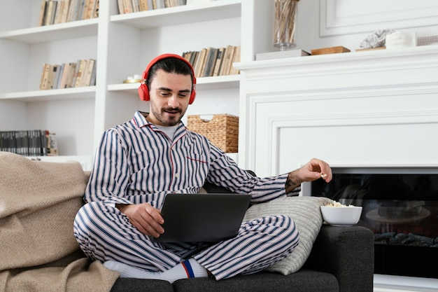노트북에서 즐거운 시간을 보내고 잠 옷에있는 남자