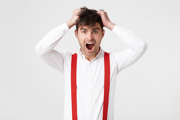 パニックに陥った男は、頭の毛に手を握りしめ、シャツと赤いサスペンダーを着て、
