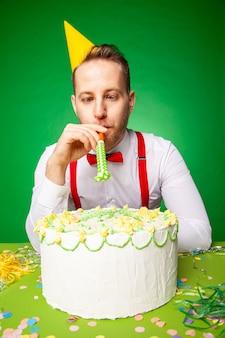 파티 모자를 쓴 남자가 달콤한 생일 케이크를 들고 테이블에 앉아 스튜디오에서 녹색 백와운드에 소음기를 불고 있다