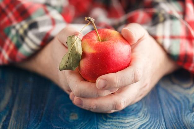 Человек в клетке держит одно яблоко
