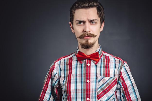 Человек в клетчатой рубашке и галстуке-бабочке в студии
