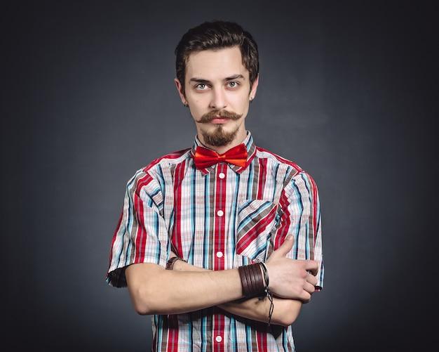 スタジオで格子縞のシャツと蝶ネクタイの男