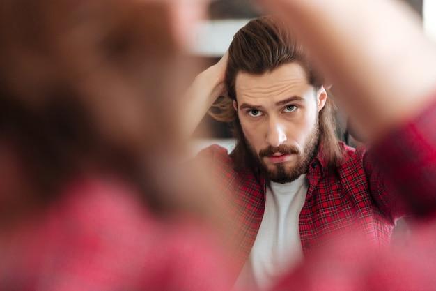 Мужчина в клетчатой рубашке стоит и смотрит в зеркало
