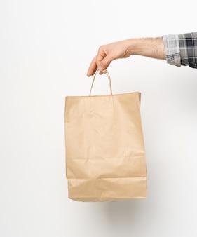 格子縞のシャツの男ツイストスリーブ手は白い壁に分離された茶色の紙袋を持っています