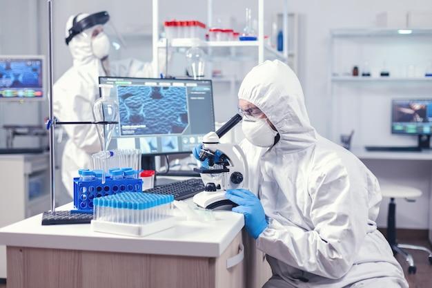 Человек в оборудовании ppe, проводящий расследование коронавируса, просматривает расследование. ученый в защитном костюме сидит на рабочем месте, используя современные медицинские технологии во время глобальной эпидемии.