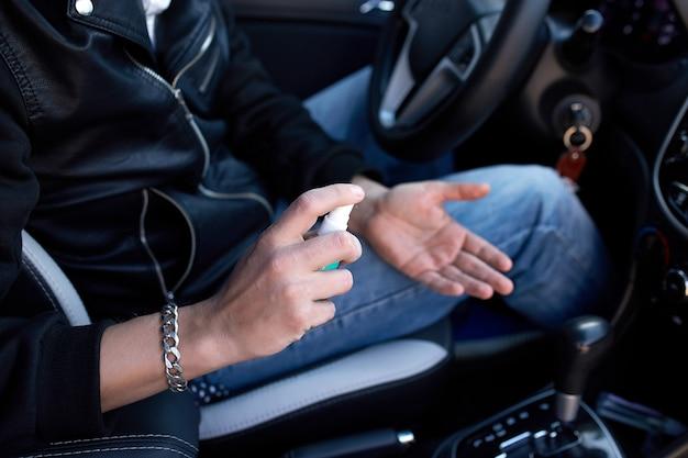 Человек в защитной маске сидит в машине, опрыскивая руки антибактериальным дезинфицирующим спреем для профилактики ишемической болезни