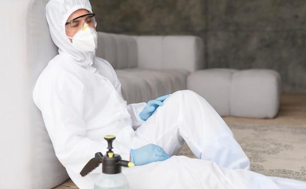 Человек в защитном костюме сидит
