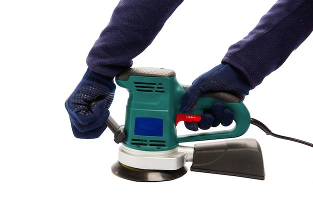 Человек в защитных синих перчатках держится за ручки эксцентрикового шлифовального станка