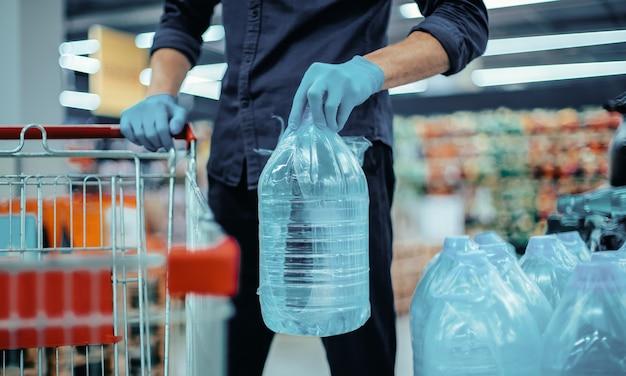 飲料水のボトルと保護手袋をはめた男